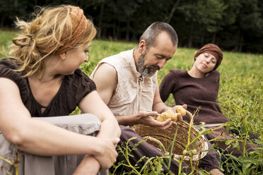 Three people sitting on field with potatoes in wicker basket - MIDF000626