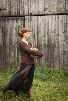 Smiling organic farmwoman holding basket with eggs - MIDF000631
