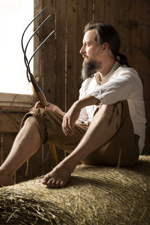 Farmer sitting with hay fork in barn - MIDF000634