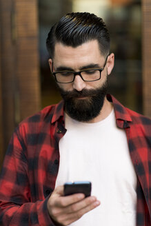 Hipster looking at his smartphone - JASF000107