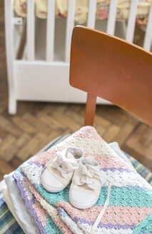 Stack of blankets and baby shoes on a chair - DEGF000524