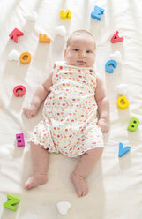 Baby girl lying on bed with wooden letters around - DEGF000525