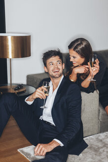 Happy young couple with glasses of champagne at sofa - CHAF001438