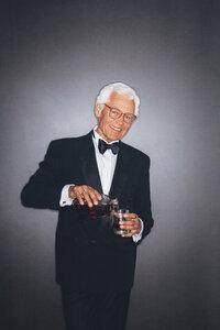 Smiling elegant senior man pouring drink into tumbler - CHAF001447