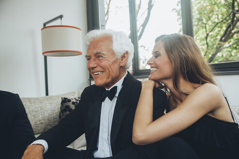 Smiling young woman with elegant senior man on couch - CHAF001464