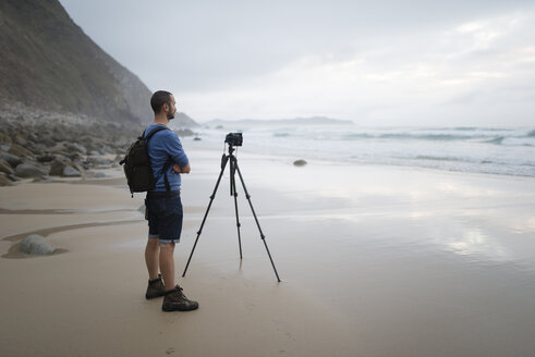 Spain, Valdovino, photographer standing on the beach taking photos with a tripod - RAEF000470
