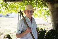 Portrait of senior man with hoe on his shoulder - RAEF000466