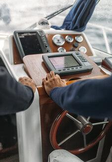 Spain, Asturias, Fishermen steering boat - MGOF000705