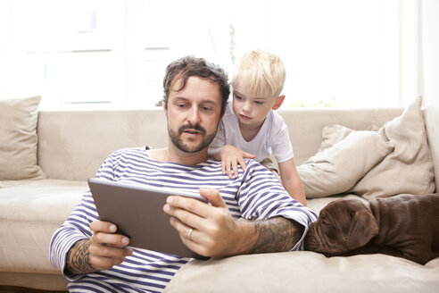 Man and his little son relaxing with digital tablet in the living room - MFRF000390