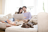 Smiling couple relaxing with laptop on the couch at living room - MFRF000394