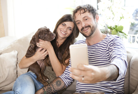 Couple sitting with Olde English Bulldogge on the couch taking a selfie with smartphone - MFRF000397
