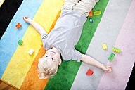 Little boy lying on striped carpet besides his building bricks - MFR000416