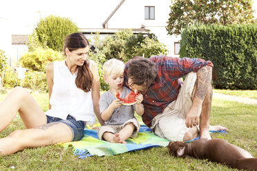 Parents sitting with their little son on a blanket in the garden eating watermelon - MFRF000433