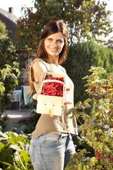 Smiling woman offering red currants in a basket - MFRF000441