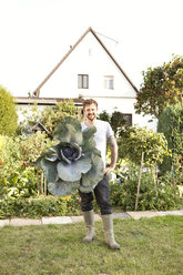 Portrait of man standing in the garden presenting red cabbage - MFRF000443