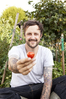 Portrait of smiling man with tatoos on his arms sitting in the garden holding tomato - MFRF000446