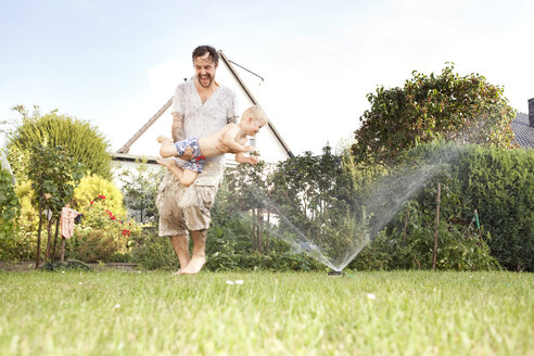 Father and his little son having fun together in the garden - MFRF000451