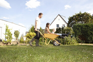 Man pushing wheelbarrow with mother and his little son through the garden - MFRF000454