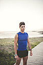 Spain, Ferrol, portrait of a jogger standing on boardwalk - RAEF000478