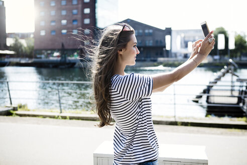Germany, Duisburg, young woman taking a selfie with smartphone - GDF000863