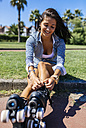 Spain, Gijon, teenage girl sitting on curb tying her roller skates - MGOF000982