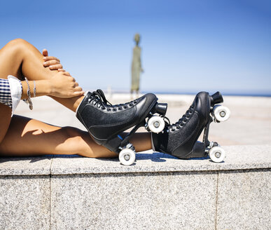 Spain, Gijon, legs of a teenage girl with roller skates sitting on a wall - MGOF000997