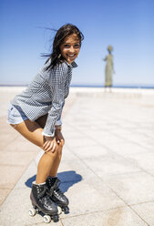 Spain, Gijon, smiling teenage girl on roller skates - MGOF000998