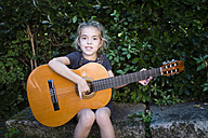 Spain, girl playing spanish guitar outdoors - RAEF000475