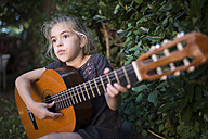 Spain, girl playing spanish guitar outdoors - RAEF000477