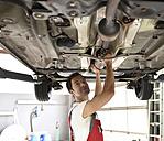 Car mechanic working in repair garage, checking underbody of a car - LYF000496