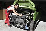 Car mechanic examining accident damaged car before repair - LYF000497