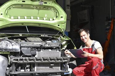 Car mechanic examining accident damaged car before repair - LYF000505
