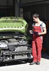 Car mechanic examining accident damaged car before repair - LYF000500