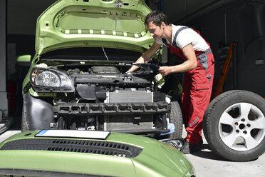 Car mechanic examining accident damaged car before repair - LYF000507