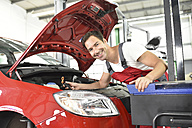 Car mechanic working in repair garage, setting car headlights - LYF000518