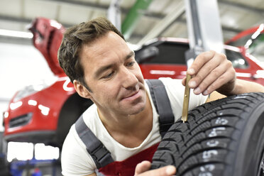 Car mechanic working in repair garage, controlling of pattern depth - LYF000522
