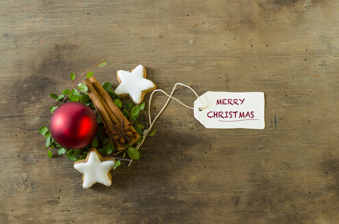 Christmas decoration with cinnamon sticks and stars and a red Christmas bauble on wood - ODF001307