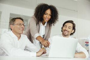 Three smiling business people in conference room looking at laptop - MFF002152