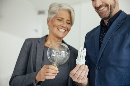 Businesswoman and businessman comparing regular and energy-saving lightbulb - MFF002158