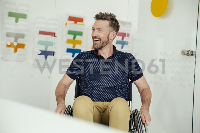 Smiling man in wheelchair in modern office - MFF002163
