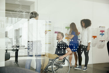 Colleagues talking in office with one sitting in wheelchair - MFF002175