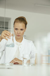 Female scientist looking at beaker with liquid - MFF002193