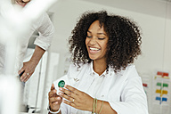 Smiling female scientist holding green plug socket in lab - MFF002208