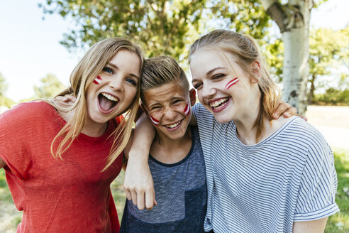 Austria, three teenagers with national colors painted on their cheeks celebrating together - AIF000008