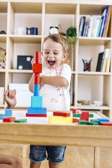 Portrait of excited little boy playing with building bricks - JRFF000059