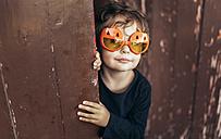 Portrait of little girl wearing halloween glasses shaped like pumpkins - MGOF000670