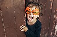 Portrait of little screaming girl wearing halloween glasses shaped like pumpkins - MGOF000671