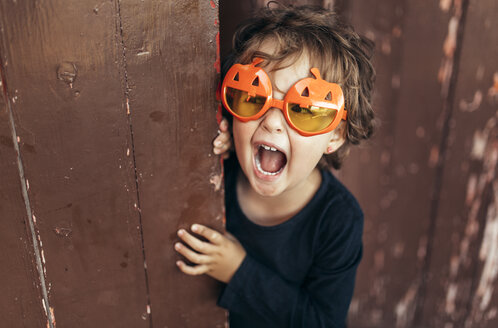 Portrait of little screaming girl wearing halloween glasses shaped like pumpkins - MGOF000671