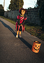 Little girl with closed eyes masquerade as a witch standing at sunlight - MGOF000675