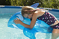Happy girl in swimming pool with inflatable dolphin - SARF002100